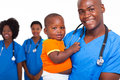 Portrait good looking african american male pediatric doctor little boy female nurses background Stock Photo