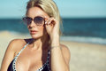 Portrait of a gorgeous blond lady in mirrored sunglasses and swimwear on the beach. Eyewear concept.