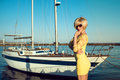 Portrait of gorgeous middle-aged blond woman wearing yellow tight-fitted lace mini dress and sunglasses standing on the yacht pier Royalty Free Stock Photo