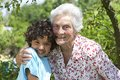 Portrait of a grandmother and her happy grandson in sunny garden Royalty Free Stock Photography
