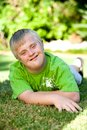 Portrait of handicapped boy on green grass. Royalty Free Stock Photo