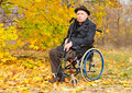 Portrait of a handicapped man in his wheelchair elderly gentleman sitting autumn sun holding pair crutches as he enjoys last warm Stock Photography