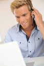 Portrait of handsome blond man talking on phone with headset smiling attractive customer service representative Royalty Free Stock Photo