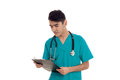 Portrait of handsome brunette male doctor in blue uniform with stethoscope posing and making notes isolated on white Royalty Free Stock Photo