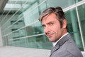 Portrait of handsome businessman standing on front of modern building Royalty Free Stock Photo