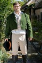 Portrait of handsome gentleman dressed in vintage costume, holding top hat in stately home courtyard Royalty Free Stock Photo