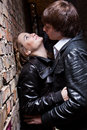 Portrait of handsome man pushes sexy woman against brick wall closeup men women Stock Photos