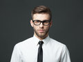 Portrait of handsome young businessman on dark background. Royalty Free Stock Photo