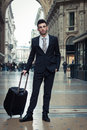 Portrait of a handsome young businessman with wheeled suitcase in suit and tie Stock Images