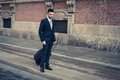 Portrait of a handsome young businessman with wheeled suitcase in suit and tie Royalty Free Stock Photo