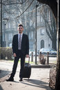 Portrait of a handsome young businessman with wheeled suitcase in suit and tie Stock Image