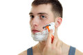 Portrait of a handsome young guy with foam on his face who carefully shaves his beard machine close-up Royalty Free Stock Photo