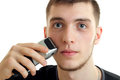 Portrait of a handsome young guy who shaves face machine and looks into the camera close-up Royalty Free Stock Photo