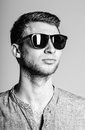 Portrait of handsome young man wearing sunglasses black and white a Stock Photos