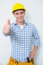 Portrait of a handyman in yellow hard hat gesturing thumbs up against white background Royalty Free Stock Photos