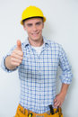Portrait of a handyman in yellow hard hat gesturing thumbs up against white background Stock Photo