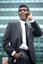 Portrait of a happy african american businessman on the phone talking outdoors Stock Photo