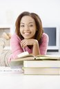 Portrait of happy afro girl college studying at home with books smiling at camera Royalty Free Stock Image