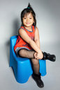 Portrait of happy asian cute girl little siting on plastic chair with gray background Royalty Free Stock Photography
