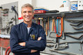 Portrait of happy auto mechanic mature in garage with tools in background Stock Photography