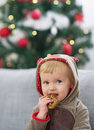 Portrait of happy baby in christmas costume eating cookie high resolution photo Stock Photography