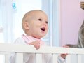 Portrait of a happy baby smiling in crib closeup Royalty Free Stock Images