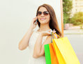 Portrait of happy beautiful young smiling woman with shopping bags colorful using and talk on the smartphone outdoors Stock Photography