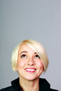 Portrait of happy blonde woman looking up at copyspace closeup on gray background Stock Photo