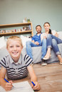 Portrait of happy boy drawing on book while parents looking at him from sofa in living room Royalty Free Stock Images