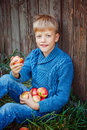 Portrait of happy boy eating an apple outside in the outdoors. Royalty Free Stock Photo
