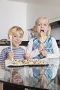 Portrait of happy boy with sister tasting spatula mix with cookie batter in kitchen Royalty Free Stock Images