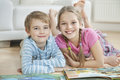 Portrait of happy brother and sister with story books while lying on floor Royalty Free Stock Photo