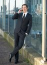 Portrait of a happy business man talking on mobile phone full length Stock Photography