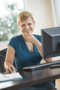 Portrait of happy businesswoman sitting at computer desk mature with hand on chin in office Royalty Free Stock Photography