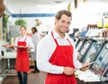 Portrait of happy butcher holding digital tablet at store with colleagues working in background Stock Photos