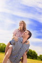 Portrait of happy caucasian couple playing outdoors in summer h having fun while piggybacking and happiness lifestyle concept Stock Photos