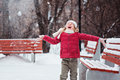 Portrait of happy child girl throwing snow on the walk in winter park red coat with wooden benches background Stock Image