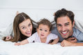 Portrait of happy couple with baby lying on bed Royalty Free Stock Photo