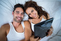 Portrait of happy couple with digital tablet lying on bed Royalty Free Stock Photo