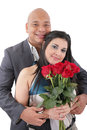 Portrait of happy couple with flowers looking at camera Stock Photography