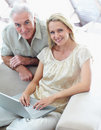 Portrait of a happy couple with laptop at home Stock Images