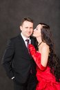 Portrait of happy couple in love posing at studio on gray background dressed in red attractive men and woman Stock Photos