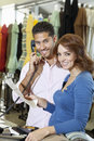 Portrait of a happy couple with man with telephone receiver and woman with paper in store Stock Images