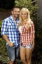 Portrait of happy couple outdoors married with attractive blonde smiling women and stubbly handsome man wearing checkered shirt Stock Photography