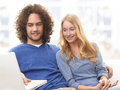 Portrait of a happy couple sitting together young spending nice relaxing day at home and surfing on the internet Royalty Free Stock Photography