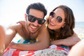 Portrait of happy couple wearing sunglasses while lying together on blanket at beach Royalty Free Stock Photo