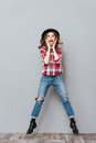 Portrait of a happy excited woman in plaid shirt jumping