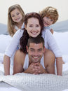 Portrait of happy family having fun in bed Stock Photos