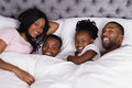 Happy young family lying together in bed