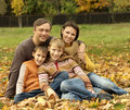 Portrait of a happy family sitting in a beautiful autumn park Royalty Free Stock Images